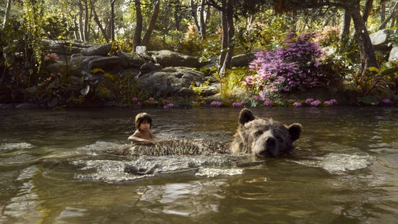 "Mowgli (Neel Sethi) and Baloo (Bill Murray) float down a river in a scene from Disney's ""The Jungle Book."""