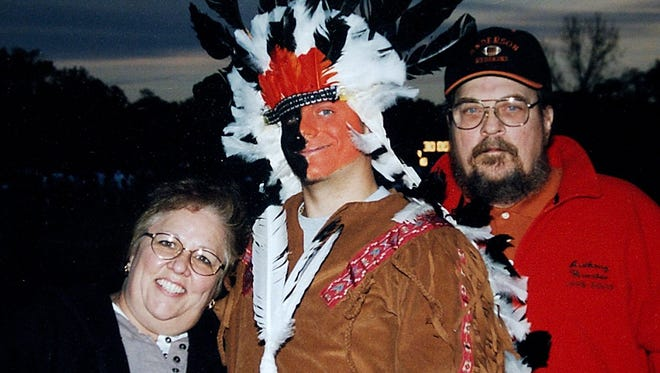 Anthony Wurster former Anderson Redskin mascot, posed with his parents Sylvia and Edward Wurster, on senior night at an Anderson High School football game. Wurster was the school's mascot, a Redskin, for five years before graduating this year. The school is eliminated the mascot beginning in the 2003-04 school year.