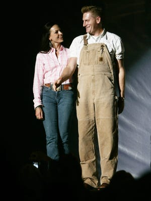 Joey Martin Feek and Rory Feek of Joey + Rory walk down the runway during the celebrity fashion show at Wildhorse Saloon on June 10, 2009.