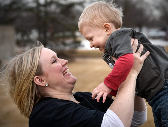 Julie Meunchow tosses her son Gavin into the air Friday,