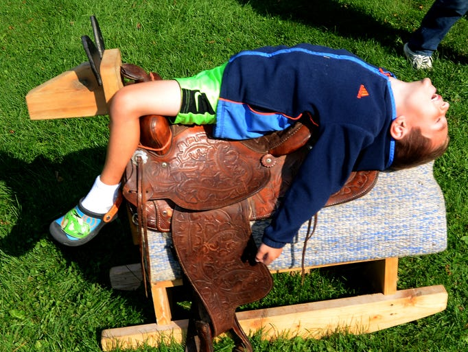 Mason Tilmos, 6, finds a unique way to relax on a rocking horse during the Sept. 20 Tollgate Fall Fair. The fair featured pond-fishing, pumpkin-decorating, cider-pressing, 4-H veggie-selling, hay-riding, hot dog-eating, and chicken-greeting fun.