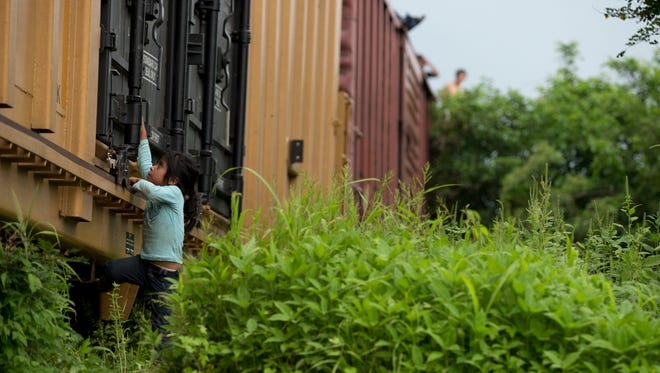 A young girl traveling with Central American migrants plays on a freight train they had been riding after a minor derailment June 20 in a remote wooded area outside Reforma de Pineda, Chiapas state, Mexico.