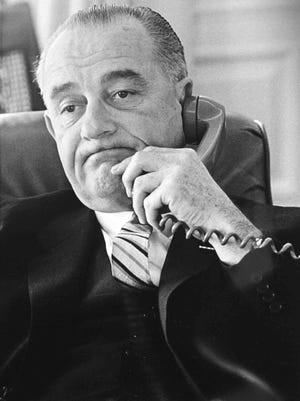 Former President Lyndon B. Johnson talks on the phone in this Jan. 10, 1964 White House file photo. In his State of the Union address two days earlier, Johnson declared a war on poverty, a term that has endured.
