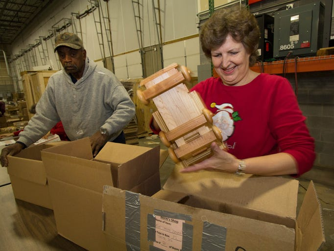Erika Kelly, Indianapolis, packs up wooden toys with members of the Central Indiana Woodworkers who met to distribute 7,229 toys to 24 agencies, Dec. 7, 2013. The non-profit group started in 1948 and worked for 11 months to make the wooden toys to distribute to needy children. The 49 volunteers met at Roche Diagnostics, Indianapolis. D. Kevin Elliott / For The Star