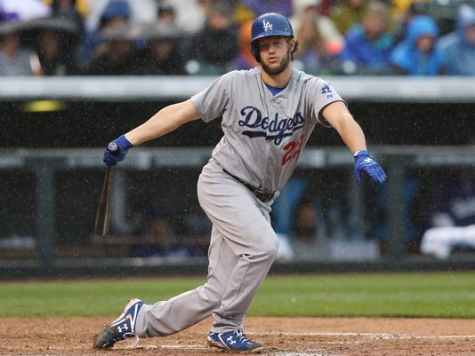 As rain falls, Los Angeles Dodgers' Clayton Kershaw strikes out  to end the top of the fifth inning against the Colorado Rockies in a baseball game in Denver on Sunday, June 8, 2014. (AP Photo/David Zalubowski)