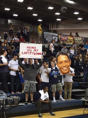Monmouth University students hold up signs before the Hawks' home-opener Sunday against Wagner.