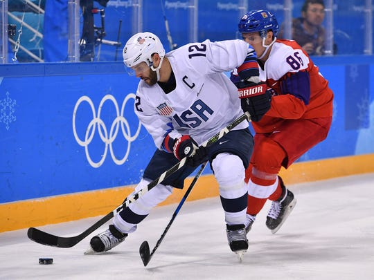 United States forward Brian Gionta (12) plays the puck