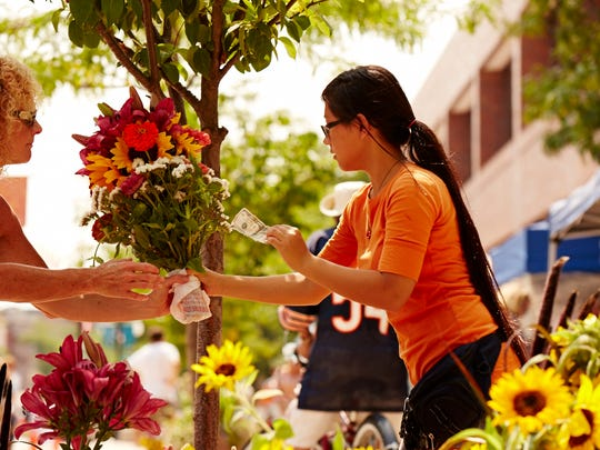 A vendor provides cut flowers to a customer during the midday Wednesday market.