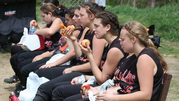 The White Plains softball team sneak in snack time