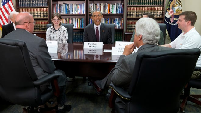 """File - In this April 3, 2015, file photo, President Barack Obama, center, participates in a roundtable about clean energy with Judy Fisher, clockwise from Obama, Marvin Lance Futch, Rep. Rob Bishop, R-Utah, Harry """"Buddy"""" Briesmaster III, Sen. Orrin Hatch, R-Utah, and Michelle Fisher at Hill Air Force Base, Utah. Last week, Futch donned a white polo and drove to Hill Air Force Base for what he believed was a chance to be in the audience during a news conference with a """"senior White House official."""" Instead, he found himself sitting at a small table just one seat away from President Barack Obama, a speck of white in a circle of dark suits. (AP Photo/Carolyn Kaster, File)"""