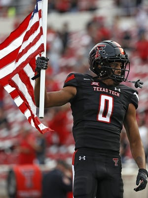 Texas Tech's Seth Collins (0) carries the American flag while leading the team onto the field before the game against Houston Baptist, Saturday, Sept. 12, 2020, at Jones AT&T Stadium in Lubbock, Texas.