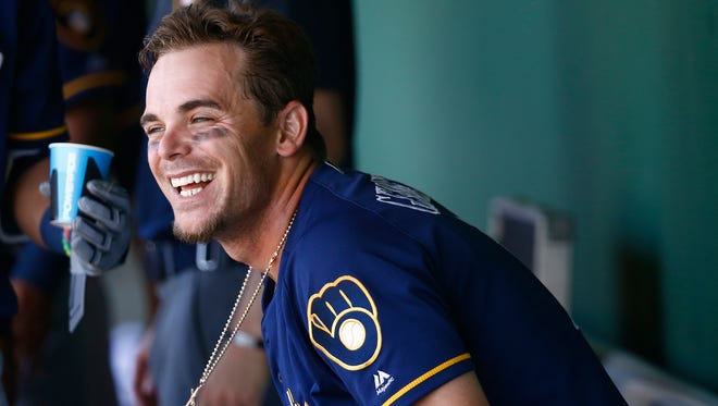 Milwaukee Brewers' Scooter Gennett smiles as he sits down in the dugout after scoring a run against the San Francisco Giants during the fifth inning of a spring training baseball game Sunday, March 19, 2017, in Scottsdale, Ariz. (
