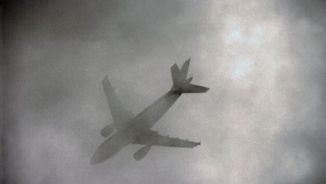 An airplane flies through spooky clouds