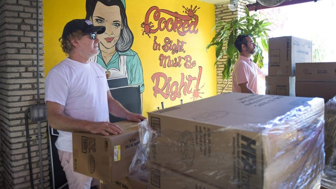 Rodney Mayo, left, moves boxes of food on March 21 as Howley's Restaurant in West Palm Beach sets up as a food distribution center. [MELANIE BELL/ palmbeachpost.com]\r
