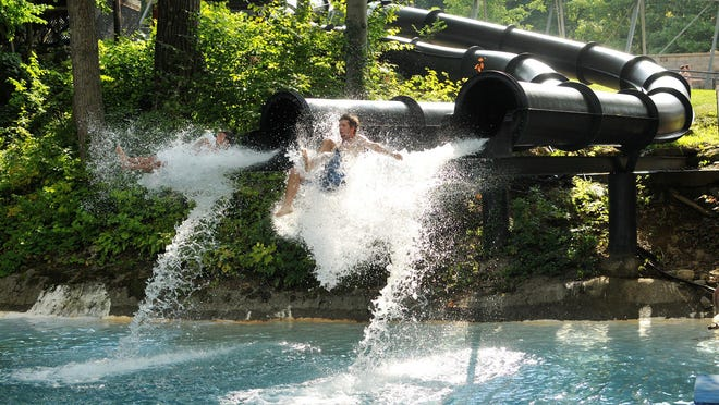 Patrons at Action Park fly out of a waterslide in this 2014 photo.