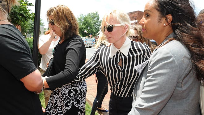 Molly Shattuck (center), a former Baltimore Ravens cheerleader charged with a sex offense against an underage teen boy arrives at the Sussex County Courthouse on Tuesday.