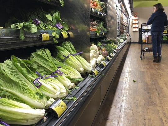 Romaine lettuce on the shelves as a shopper walks through the produce area of an Albertsons market Tuesday, Nov. 20, 2018, in Simi Valley, Calif.