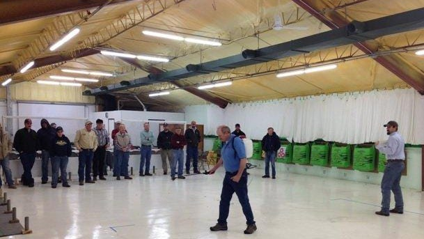 Attendees look on as Travis Standley, Teton County Extension Agent, far right, demonstrates sprayer calibration during the pesticide applicator training held in Shelby.