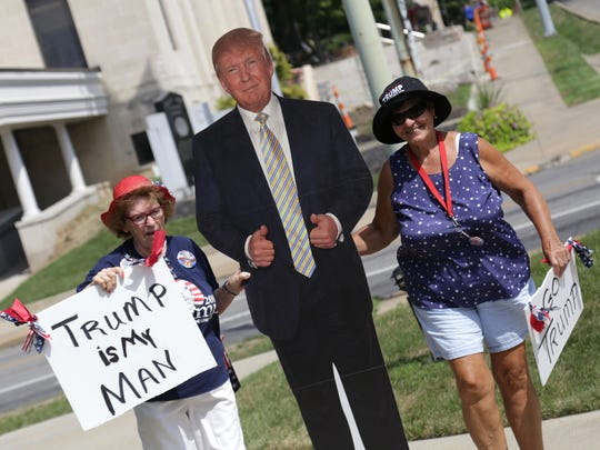 Dee Saterfield and Christina Rashaw brings a cutout of Donald Trump for a rally at Ringler Park in Ashland on Saturday.