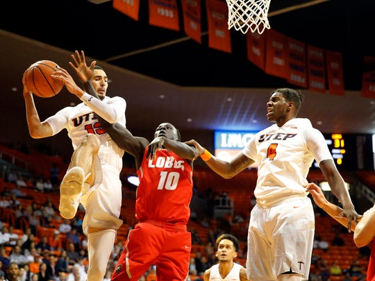 UTEP guard Isiah Osborne goes up for the rebound during first half action of play agains the New Mexico Lobos Saturday night in the Don Haskins Center. UNM Lobo Makuach Maluach attempts to knock the ball out of Osborne's hand as UTEP forward Tirus Smith looks on.