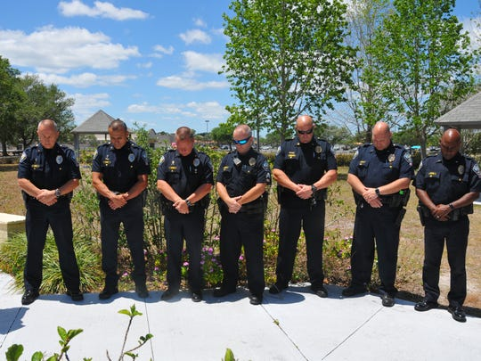 Palm Bay police officers bow their heads during a prayer
