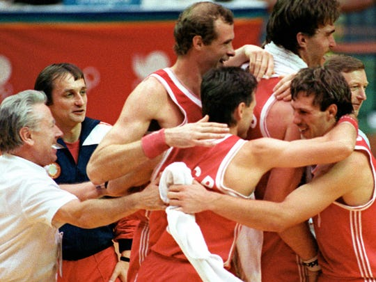 Coach Alexander Gomelsky (L) and his team celebrating their 82-76 victory over the United States in the semi-final match of the Olympic Games in Seoul.