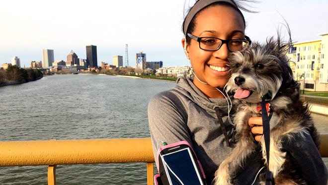Keri Omphroy takes her dog, Mojito, for a walk near her downtown loft.