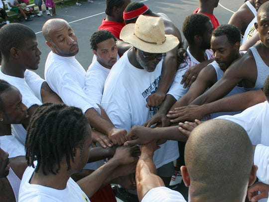 Cornell Bradley, top center, huddled with the teams before each game during the Dirt Bowl Basketball Tournament at the Shawnee Park courts.  June 27, 2009