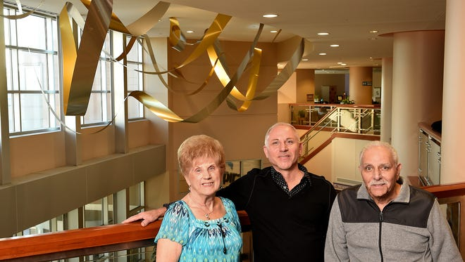 """Artist Richard Monteleone (center) with parents, Lillian and Jerry, in front of his """"Illumination"""" sculpture at Inspira Medical Center Vineland."""