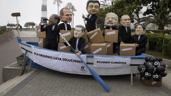 Climate activists mock world leaders Friday in Lima, Peru.