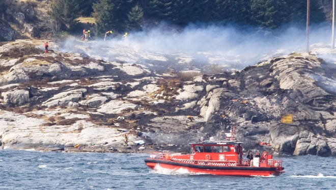 Rescuers work at the shore west of Bergen, Norway, on April 29 after a helicopter transporting workers from an offshore oil field in the North Sea crashed.