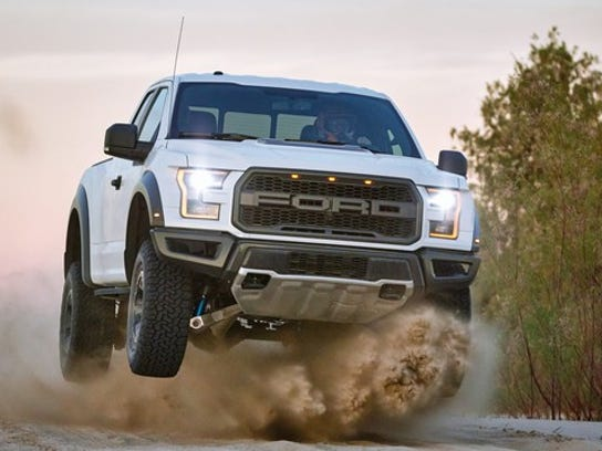A white 2017 Ford F-150 Raptor at speed in an off-road setting.