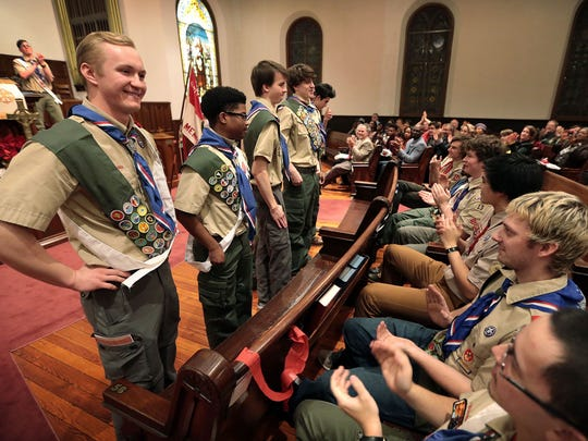 Samuel Warren (left) and Julius Self join the rest of the new Troop 13 Eagle Scouts for an ovation by family and fellow scouts during a ceremony at First Presbyterian Church.