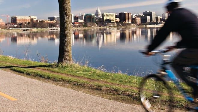 A cyclist rides on the John Nolen Path along Lake Monona in Madison.