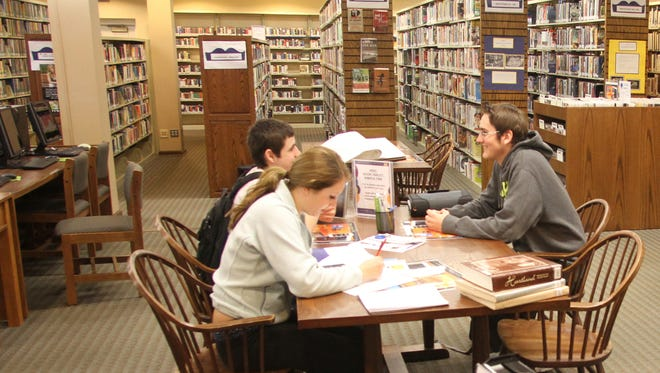 WCC students Madison Light, Logan Benner and Ryan Coleman work on their profile essays which explore the importance of Cromaine District Library to it's surrounding communities.