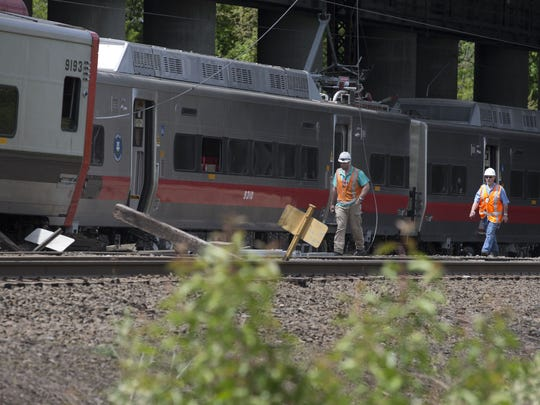 State investigators examine the scene of a May 17, 2013, Metro-North train collision in Fairfield, Connecticut.