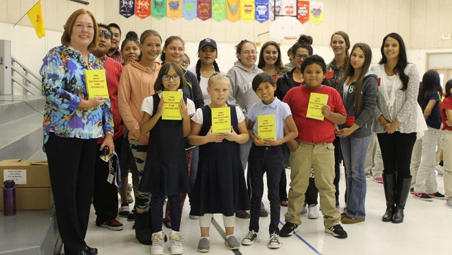 Students in the San Juan College Adult Education presented dictionaries to McCormick Elementary School Principal Lyn White, far left, and third-grade students at the school on Thursday as part of the Look It Up project.