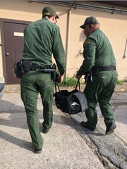 Border Patrol agents carry a duffel bag containing a tiger cub on Monday, April 30, 2018.