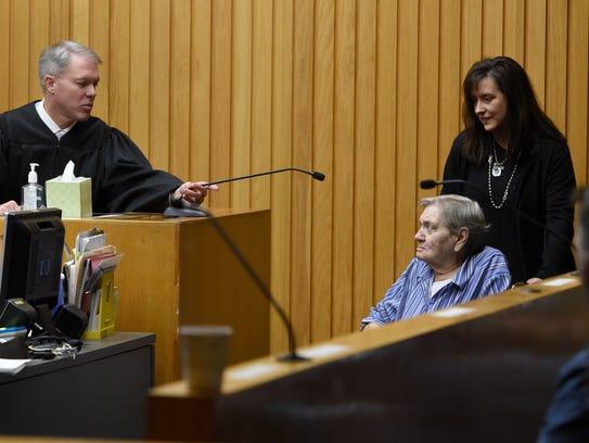 Witness coordinator Kim Strike rolls a witness into