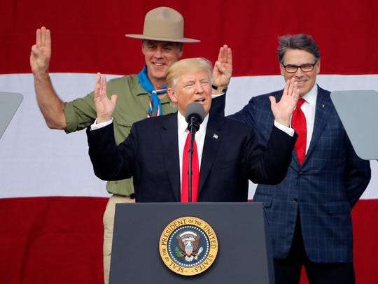 President Donald Trump gestures as former Boys Scouts,
