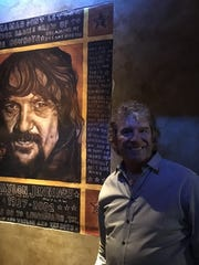 Bob Sikora stands by a painting of Waylon Jennings