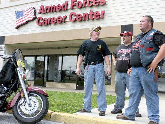 Members of the group Three Percenters Pennsylvania carry firearms outside the Armed Forces Career Center in the Manchester Crossroads shopping center on July 20 as part of a campaign to defend military personnel, who are barred from carrying weapons on the job.