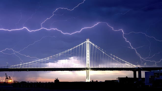 Lightning forks over the San Francisco-Oakland Bay Bridge as a storm passes over Oakland on Sunday. Numerous lightning strikes early Sunday sparked brush fires throughout the region.