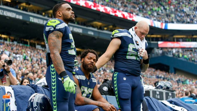 Seattle Seahawks defensive end Michael Bennett (72) sits during the national anthem as Seahawks running back Thomas Rawls (34) and center Justin Britt (68) stand next to him prior to kickoff against the San Francisco 49ers during the first quarter at CenturyLink Field.