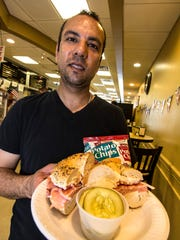 Owner Mohy Sabry with sliced fresh Nova on a bagel.