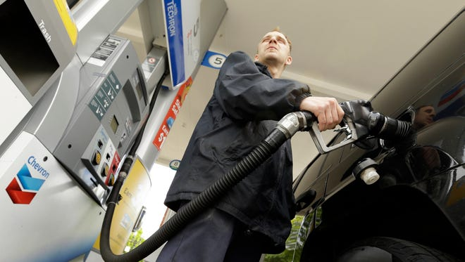 Attendant James Lewis pumps gas at a station in Portland, Ore., Wednesday, May 6, 2015. Oregon is one of just two states where motorists aren't allowed to pump their own gas. The other is New Jersey.  Now the Oregon Legislature appears ready to at least let people driving through rural Oregon pump their own. (AP Photo/Don Ryan)