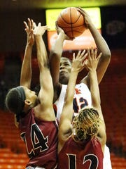 UTEP's Tamara Seda, center, reaches high in an effort to get a shot past Brianna Freeman, left, and Zaire Williams of NMSU Thursday night in the Don Haskins Center.