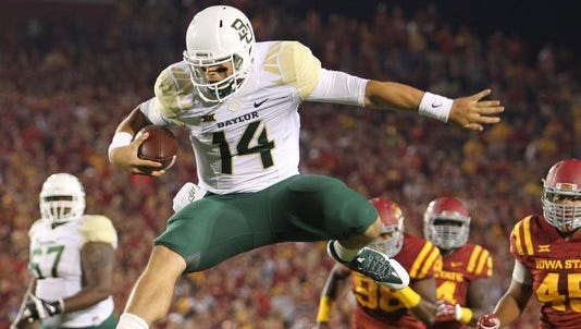 Baylor quarterback Bryce Petty (14) leaps over Iowa State Cyclones defensive back Kamari Cotton-Moya for a touchdown.