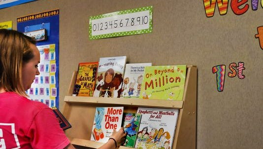 First-grade teacher Elizabeth Polley organizes her classroom for the first day of school at Wayne Township's Stout Field Elementary School. Friday, Aug. 1, is the first day of the 2014-2015 school year for students at the school.