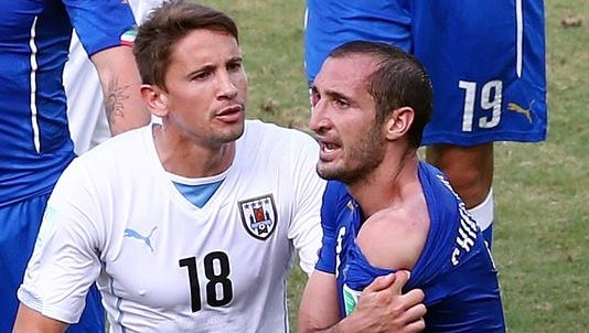 Giorgio Chiellini of Italy pulls down his shirt after a clash with Luis Suarez of Uruguay (not pictured) as Gaston Ramirez of Uruguay looks on during Tuesday's Group D Match. Uruguay won with a goal in the 81st minute, 1-0.